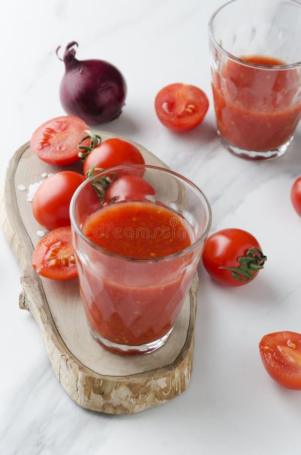 Vidrio de jugo de tomate sano con las sustancias del minearl Tomates frescos en la tabla blanca, foto vertical imagen de archivo libre de regalías