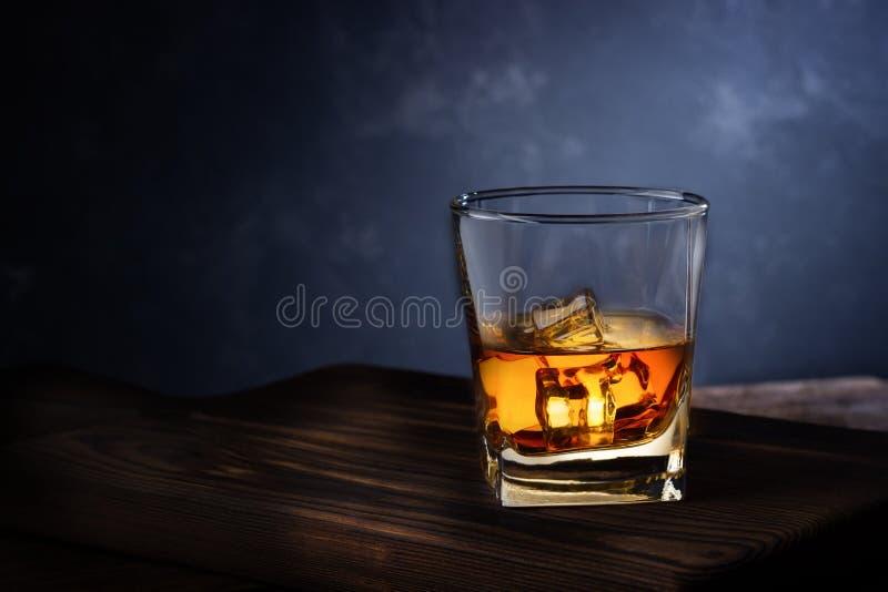 Vidrio de la bebida del alcohol con hielo en la tabla de madera fotos de archivo