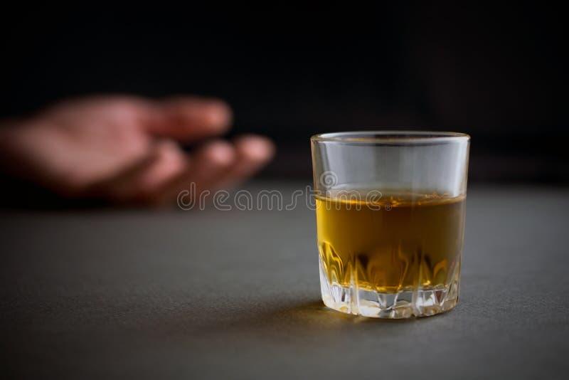 Vidrio de la bebida del whisky o del coñac o del alcohol, mano de un hombre borracho fotos de archivo libres de regalías