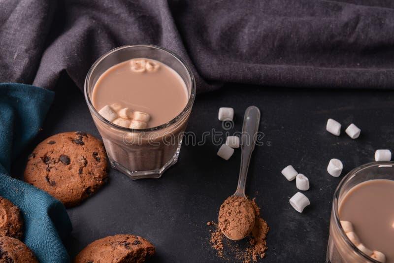 Vidrio de la bebida deliciosa del cacao con las melcochas y las galletas en la tabla fotos de archivo