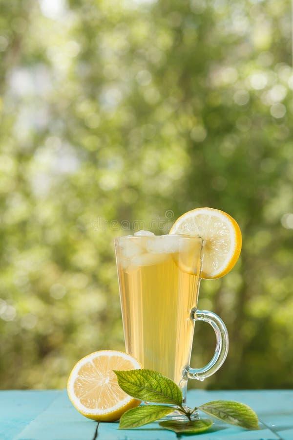 Vidrio de la bebida fría con hielo y el limón en la tabla foto de archivo libre de regalías