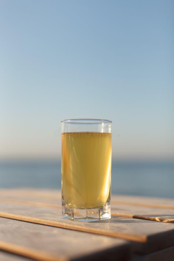 Vidrio de la bebida fría en sunbed o tabla en la playa fotografía de archivo libre de regalías