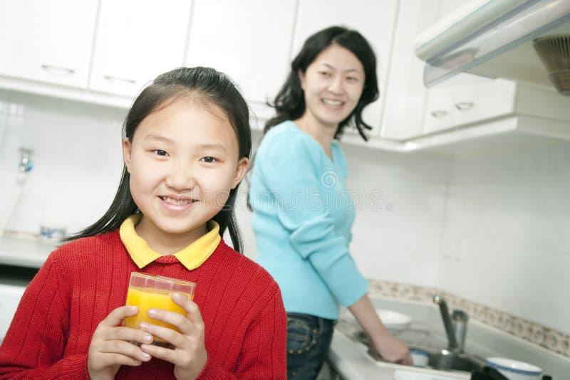 Vidrio de la explotación agrícola de la chica joven de zumo de naranja fotos de archivo libres de regalías