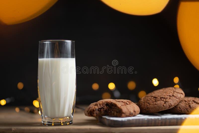 Vidrio de la foto de la leche con las galletas hechas en casa, fondo hermoso con las luces en la falta de definición imagen de archivo