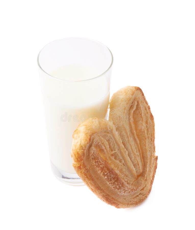 Vidrio de la leche y de la galleta en forma de corazón imagen de archivo