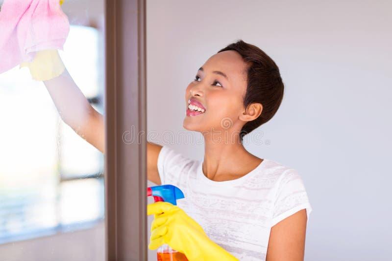 Vidrio de la puerta de la limpieza de la mujer foto de archivo