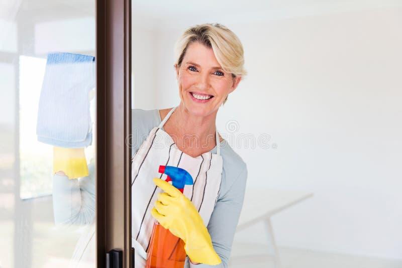 Vidrio de la puerta de la limpieza de la mujer imagen de archivo