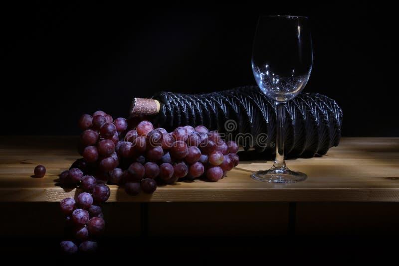 Vidrio de la uva y botella de vino fotos de archivo