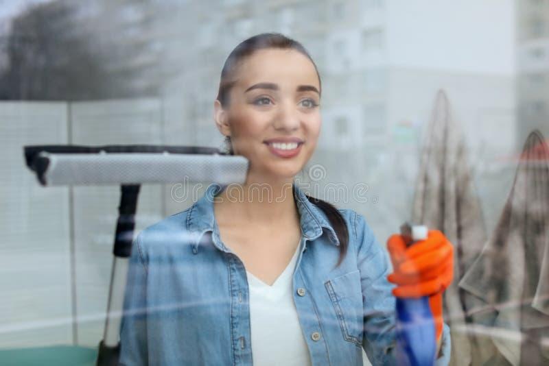 Vidrio de la ventana de limpieza de la mujer joven en casa foto de archivo libre de regalías