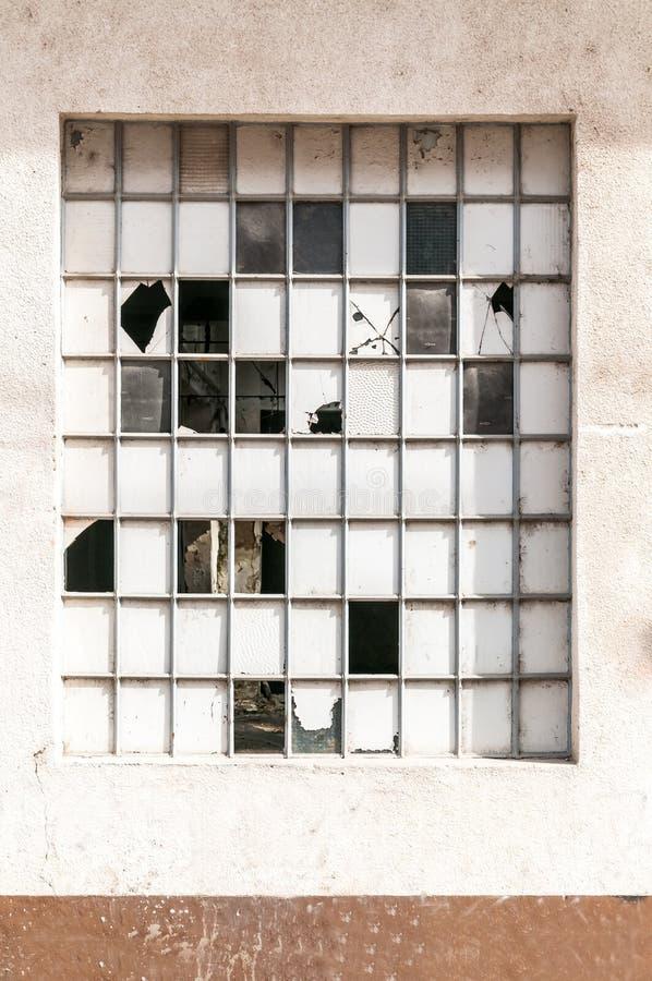 Vidrio de la ventana quebrado y dañado en el edificio viejo de la fábrica o del almacén, imagen vertical fotos de archivo