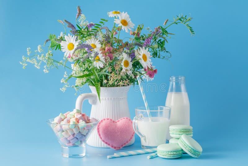 Vidrio de leche con los dulces y los macarrones rayados de la paja imagenes de archivo