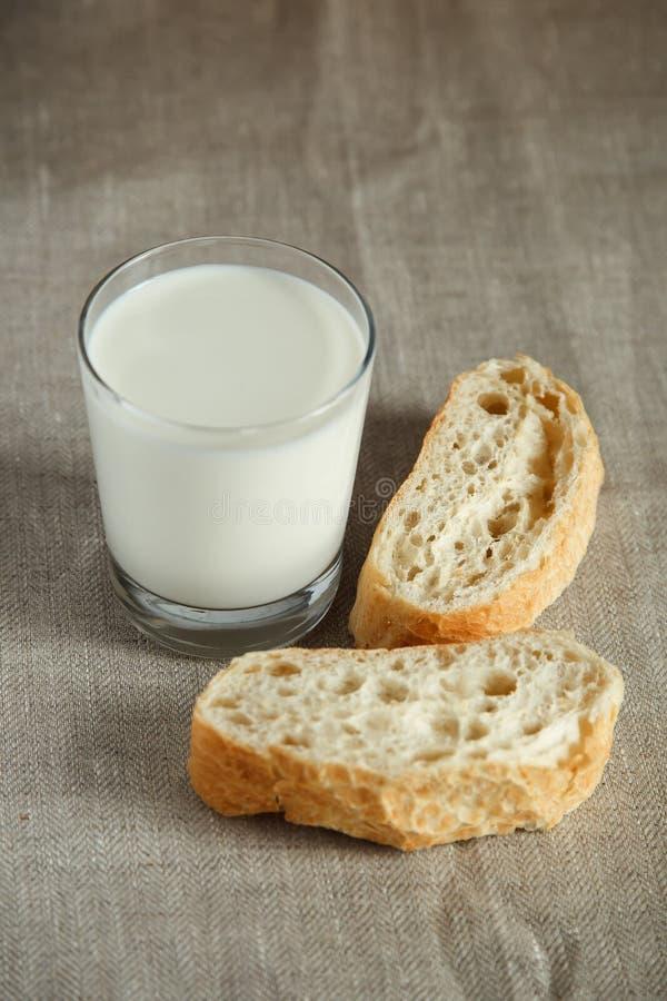 Vidrio de leche con pan fresco imagen de archivo