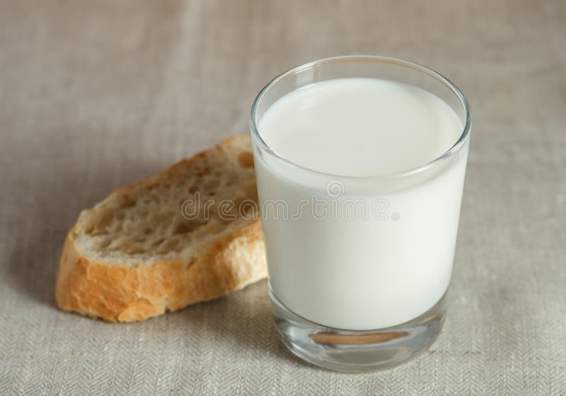 Vidrio de leche con pan fresco fotos de archivo