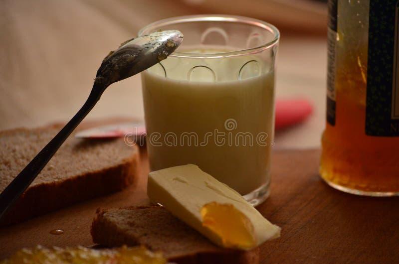 Vidrio de leche fresca, de cuchara con el atasco del albaricoque y de mantequilla fotos de archivo