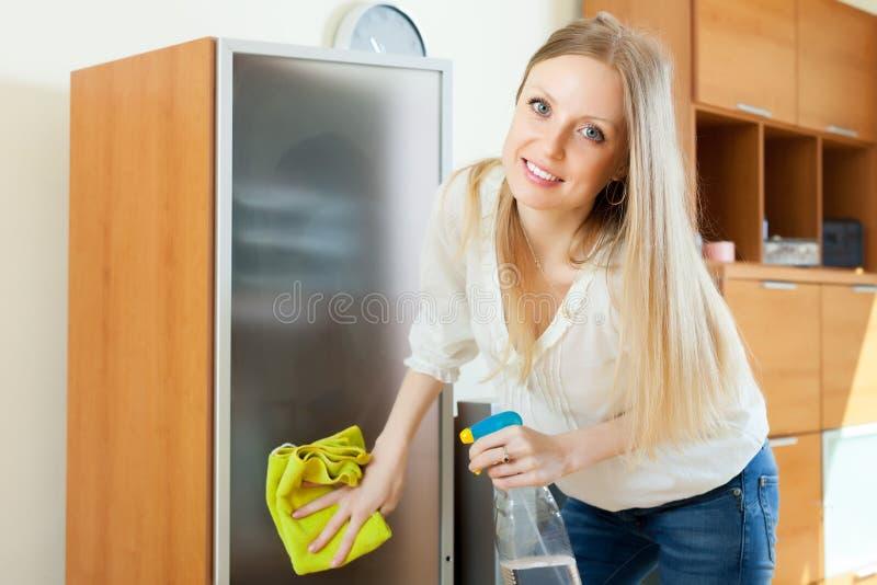 Vidrio de limpieza de la muchacha rubia de pelo largo fotos de archivo