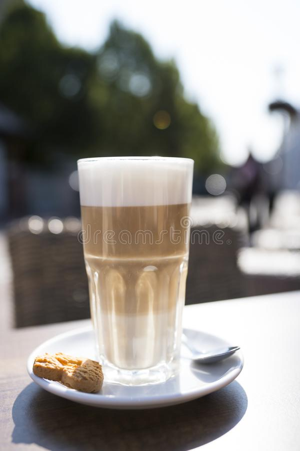 Vidrio de macchiato del latte con la espuma, la cuchara y la galleta imagen de archivo