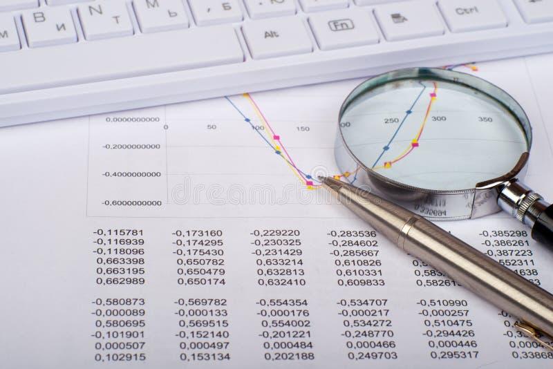 Vidrio de mano en documentos con el teclado blanco imagen de archivo libre de regalías