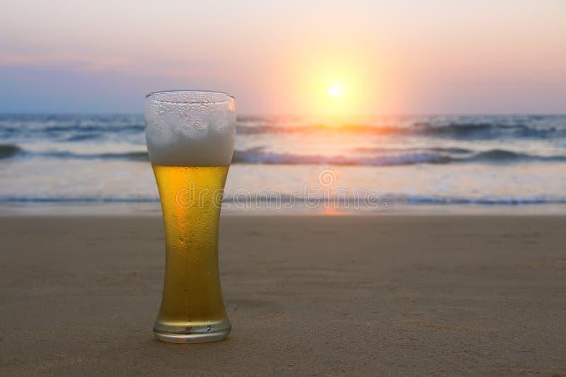 Vidrio de Misted de cerveza fr?a de Chang en la arena en el fondo del paisaje marino, del cielo de la puesta del sol y de las ond imagen de archivo
