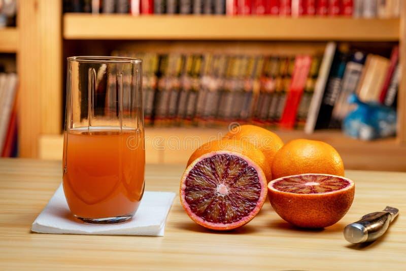 Vidrio de naranjas rojas del jugo, del cuchillo y del corte en una tabla de madera ligera Estantes de librería borrosos en el fon foto de archivo libre de regalías
