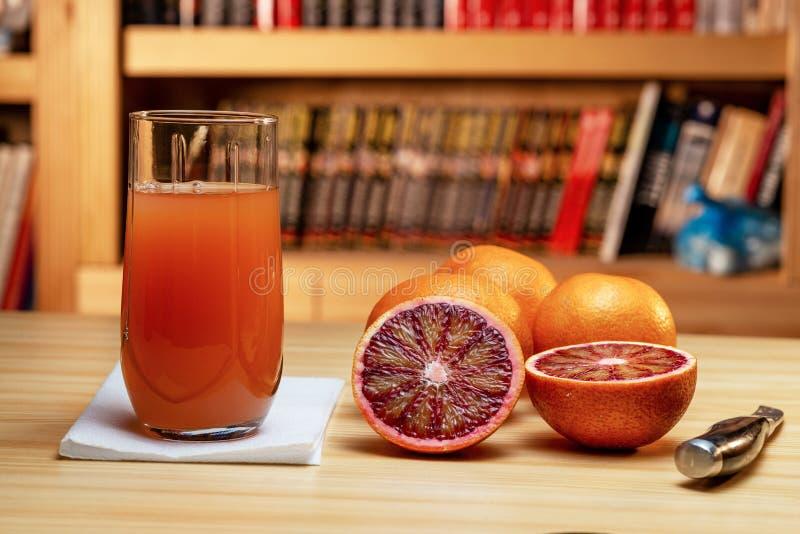 Vidrio de naranjas rojas del jugo, del cuchillo y del corte en una tabla de madera ligera Estantes de librería borrosos en el fon imágenes de archivo libres de regalías