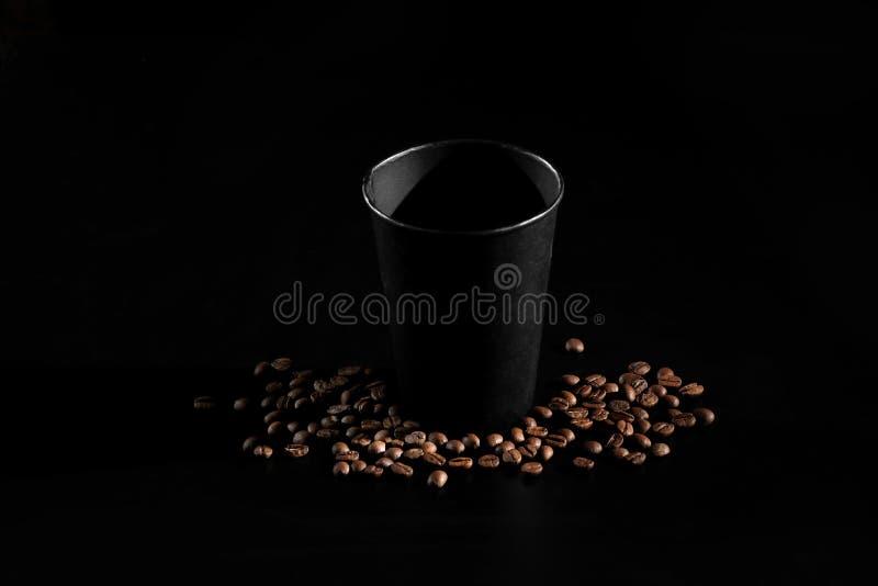 Vidrio de papel negro en fondo negro Granos de café en un fondo oscuro Buenos días imágenes de archivo libres de regalías