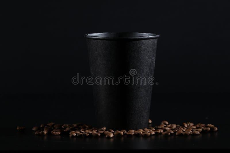 Vidrio de papel negro en fondo negro Granos de café en un fondo oscuro Buenos días imagenes de archivo