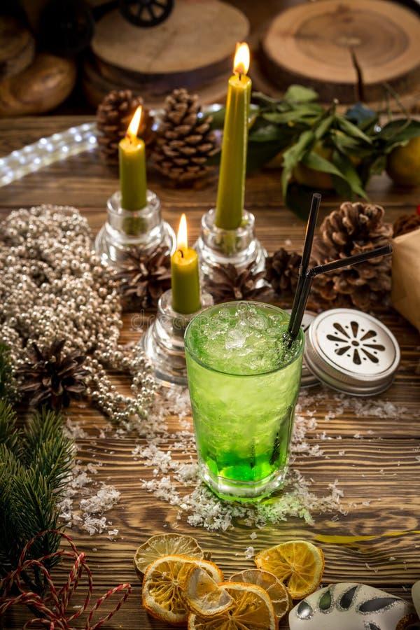 Vidrio de soda verde del limón con hielo en la tabla de madera en fondo adornado la Navidad imagenes de archivo
