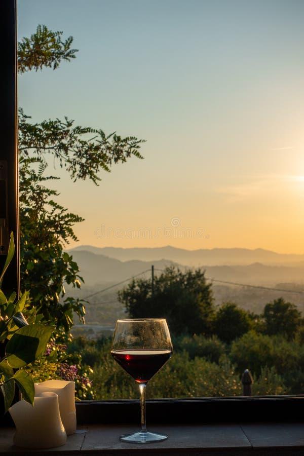 Vidrio de soportes del vino tinto en una ventana en Toscana imagen de archivo