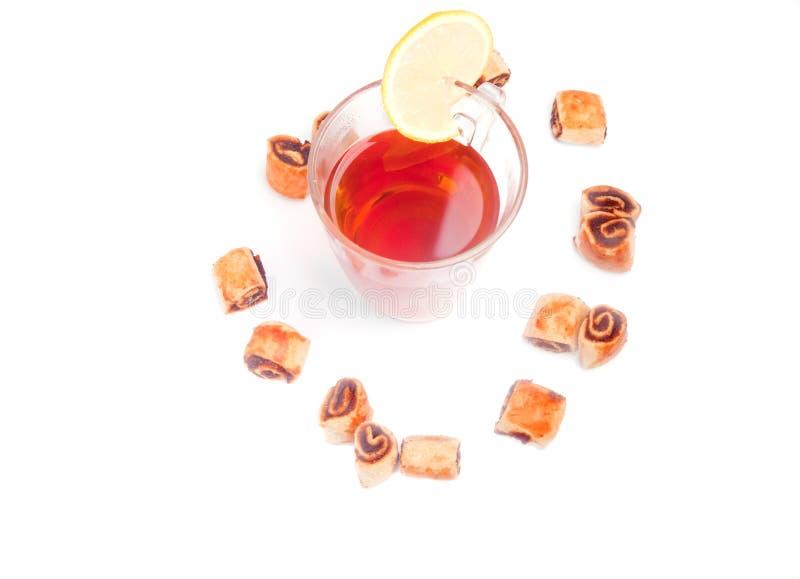 Vidrio de té con las galletas alrededor imagenes de archivo