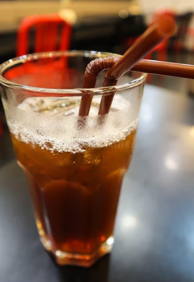 Vidrio de té del limón del hielo con dos paja marrón en la tabla negra en el restaurante Un vidrio para dos, junto Imagen del con foto de archivo libre de regalías