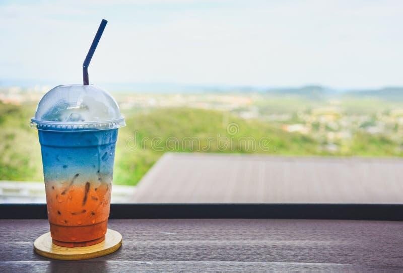 Vidrio de té tailandés helado colorido de la leche mezclado con el jugo del guisante de mariposa en la tabla de madera con el fon fotos de archivo