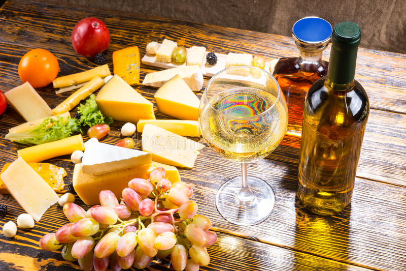 Vidrio de vino blanco en la tabla con diversos quesos foto de archivo