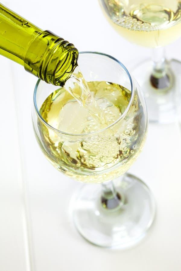 Vidrio de vino blanco que es vertido foto de archivo