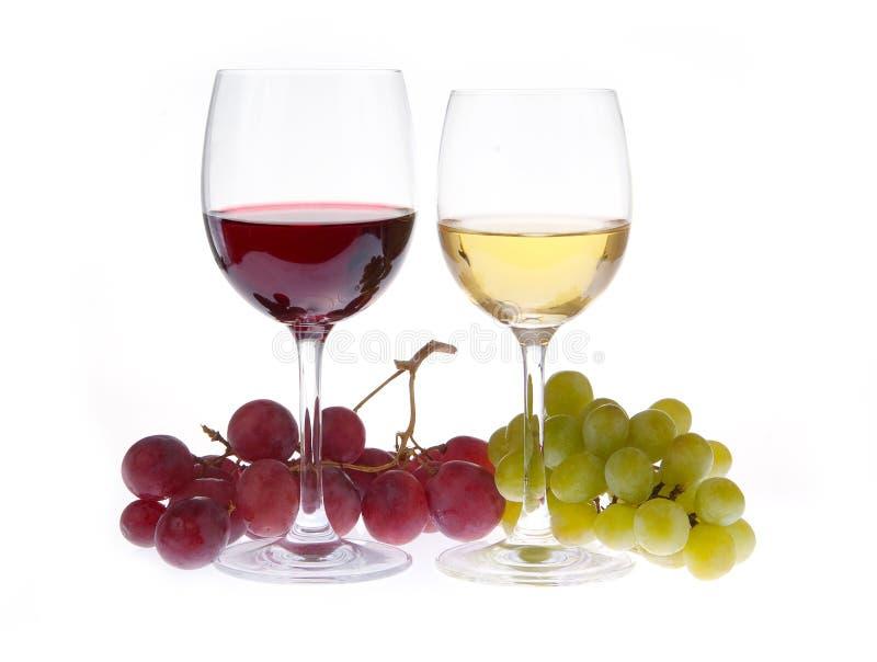 Vidrio de vino blanco rojo y con las uvas foto de archivo
