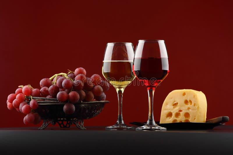 Vidrio de vino blanco rojo y, de uvas y de queso foto de archivo libre de regalías