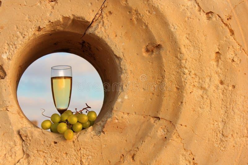 Vidrio de vino blanco y un manojo de uvas dentro de una piedra de molino imágenes de archivo libres de regalías