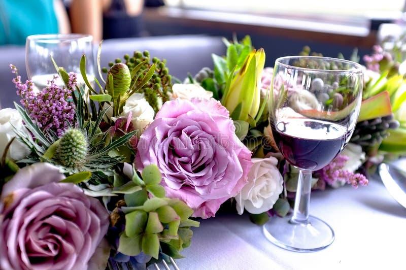 Vidrio de vino colocado al lado de las flores imagen de archivo