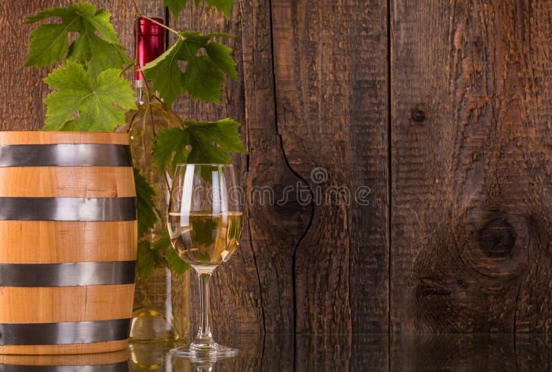 Vidrio de vino con la botella blanca del barril detrás de grapeleaves imagen de archivo libre de regalías
