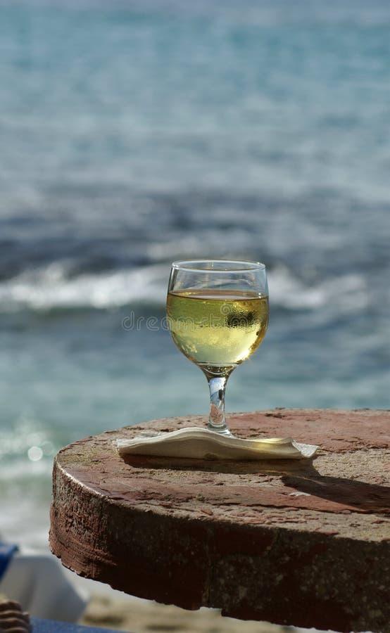 Vidrio de vino en la playa imagen de archivo