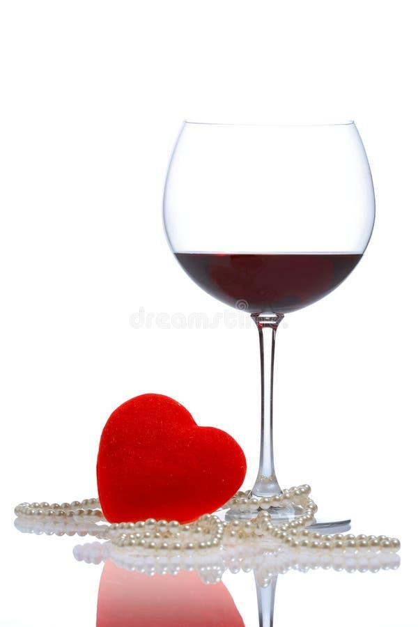 Vidrio de vino, perlas y un corazón rojo (camino de recortes incluido) imagenes de archivo