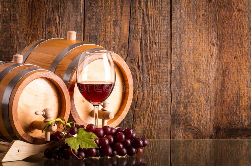 Vidrio de vino rojo con dos barriles y uvas imagen de archivo
