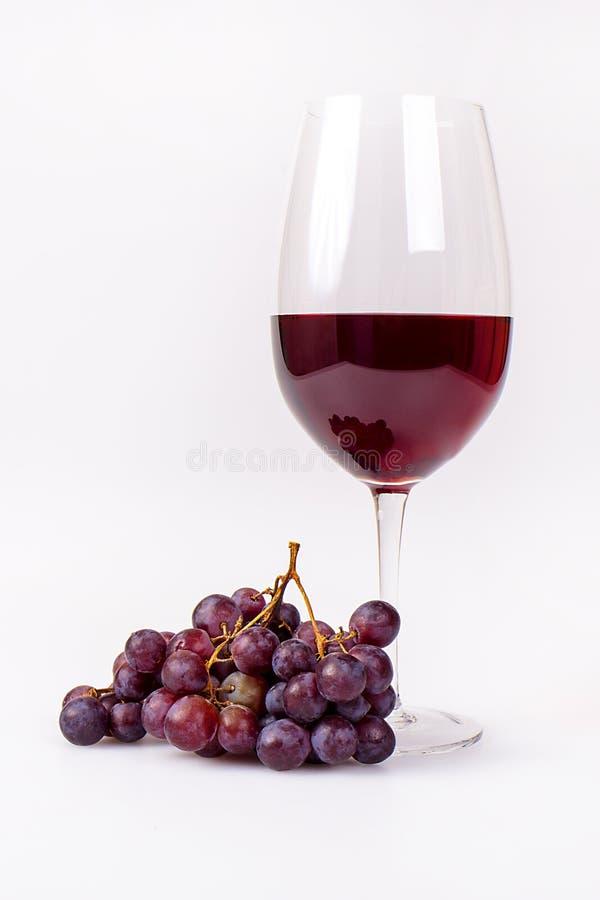 Vidrio de vino rojo con el manojo de las uvas foto de archivo