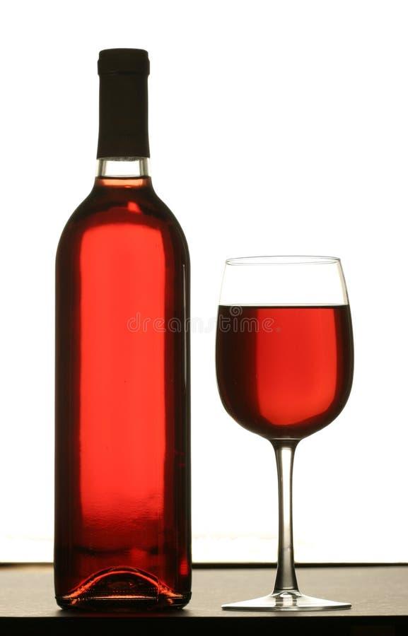 Vidrio de vino rojo con la botella de vino imagen de archivo libre de regalías