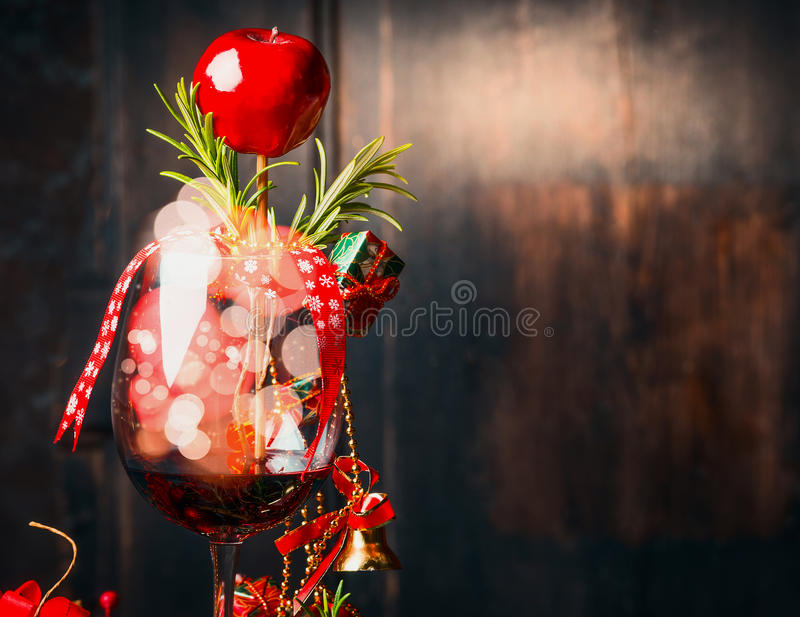 Vidrio de vino rojo con la decoración de la Navidad y de bokeh en vidrio en fondo de madera oscuro foto de archivo libre de regalías