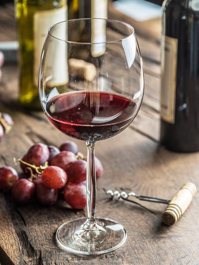 Vidrio de vino rojo en la tabla Botella y uvas de vino en los vagos fotografía de archivo