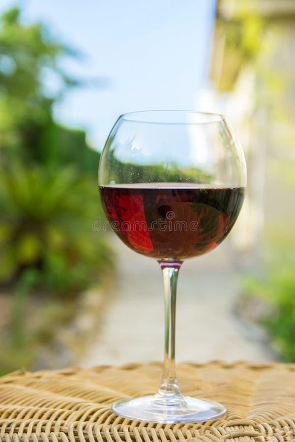Vidrio de vino rojo en la tabla de mimbre de la rota en jardín en la mansión del chalet Primavera brillante Sunny Day Vegetation  foto de archivo