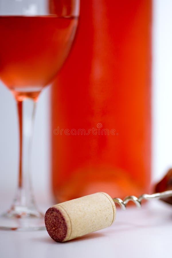 Vidrio de vino rosado con la botella, el sacacorchos y el fondo blanco foto de archivo libre de regalías