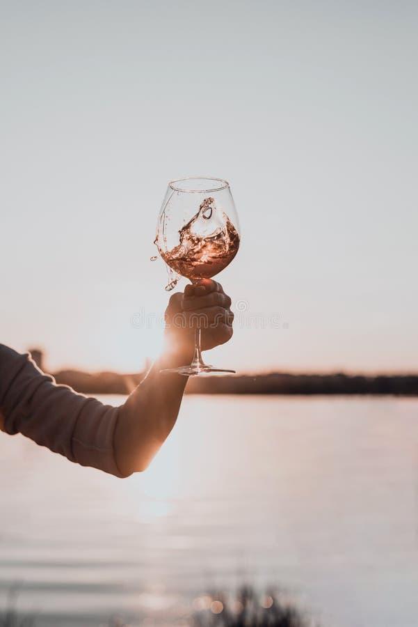 Vidrio de vino rosado en la mano de la mujer contra el cielo de la puesta del sol foto de archivo