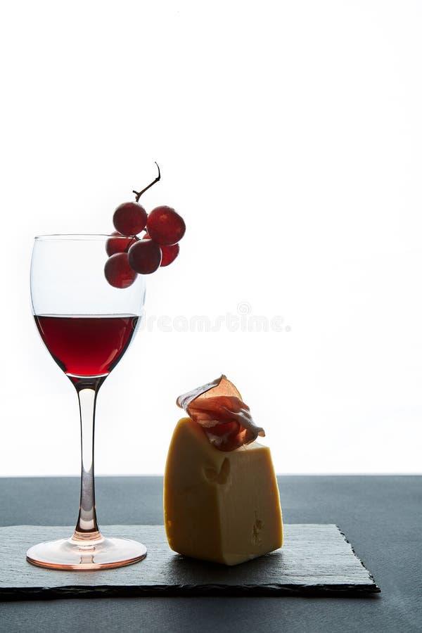 Vidrio de vino tinto al lado de la botella y del aperitivo tradicional en el fondo blanco fotos de archivo libres de regalías