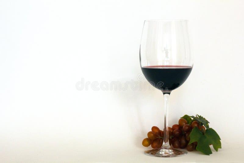 Vidrio de vino tinto con un manojo de uvas fotos de archivo libres de regalías